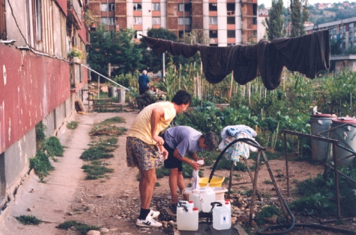 "Foto: Ivana Maček. Publicerad i Sarajevo Under Siege: Anthropology in Wartime av Ivana Maček (University of Pennsylvania Press, 2009). ""Washing and filling water containers at the hose that was the only source of water for the entire neighborhood. In the background lawns have been planted with vegetables. Sarajevo suburb of Hrasno, September 1994""."